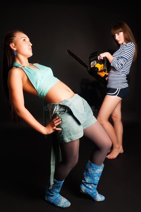 Niebezpieczeństwo dziewczyna z piłą łańcuchową zdjęcie stock