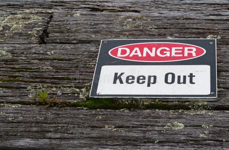 Niebezpieczeństwo, utrzymuje out znaka ostrzegawczego nad starym wietrzejącym nieociosanym drewnianym t obrazy royalty free