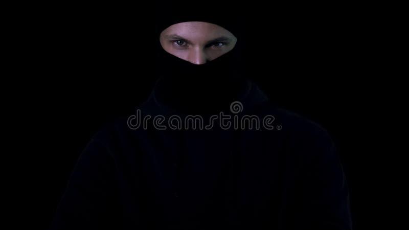 Niebezpieczna samiec patrzeje in camera na czarnym tle w balaclava, terroryzm zdjęcia stock