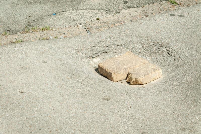 Niebezpieczna szkoda na asfaltowej drodze z cegłami w otwartym dziury niebezpieczeństwie dla pojazdu jeżdżenia zdjęcie stock