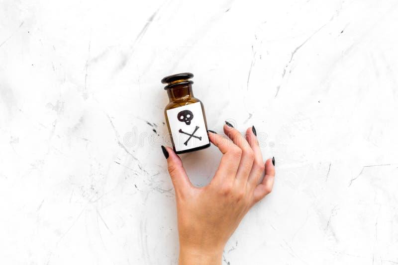 Niebezpieczni nałogi, niebezpieczna rozrywka jad Żeńska ręka chwyta butelka z czaszką i crossbones na bielu kamieniu zdjęcia royalty free
