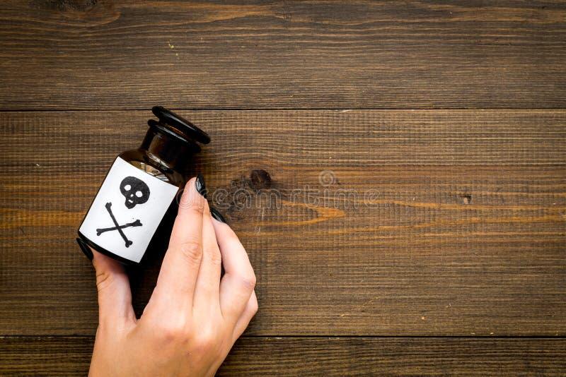 Niebezpieczni nałogi, niebezpieczna rozrywka jad Żeńska ręka chwyta butelka z czaszką i crossbones na ciemny drewnianym obrazy stock
