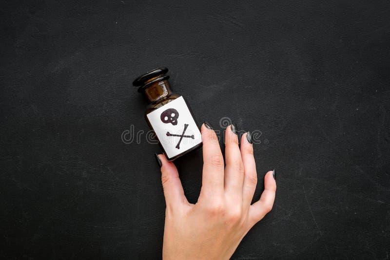 Niebezpieczni nałogi, niebezpieczna rozrywka jad Żeńska ręka chwyta butelka z czaszką i crossbones na czerni fotografia stock