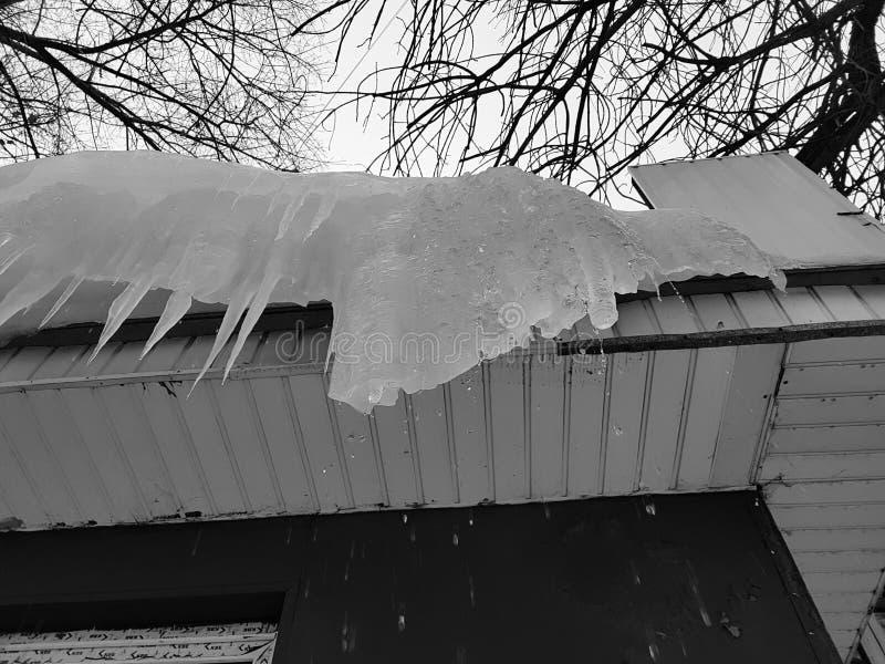 Niebezpieczni sople i lód na dachu w wiośnie lub zimie fotografia stock