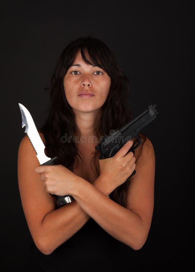 Niebezpieczny kobiety mienia nóż i pistolet obrazy royalty free