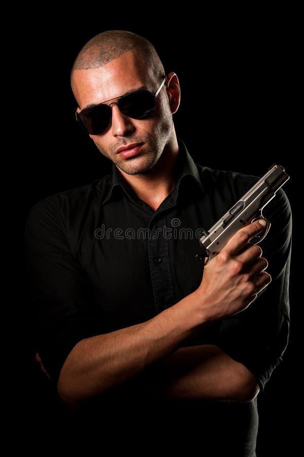 Niebezpieczny mężczyzna z pistoletem i okularami przeciwsłonecznymi zdjęcie stock