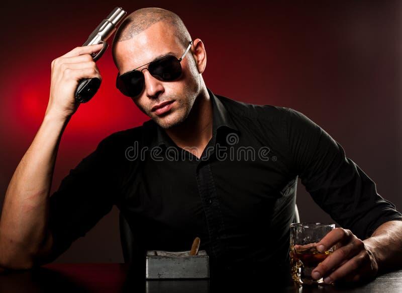 Niebezpieczny mężczyzna z pistoletem i okularami przeciwsłonecznymi obraz royalty free