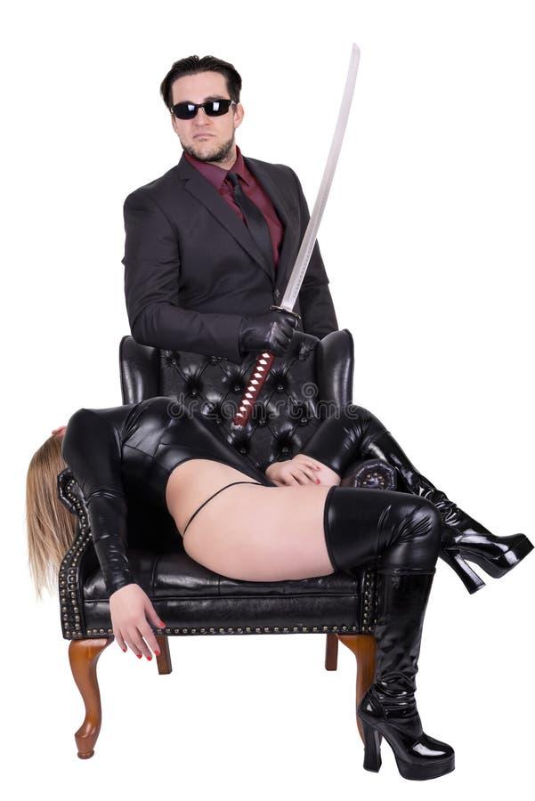Niebezpieczny zabójca z katany i kobiety łgarskim puszkiem w krześle zdjęcia royalty free