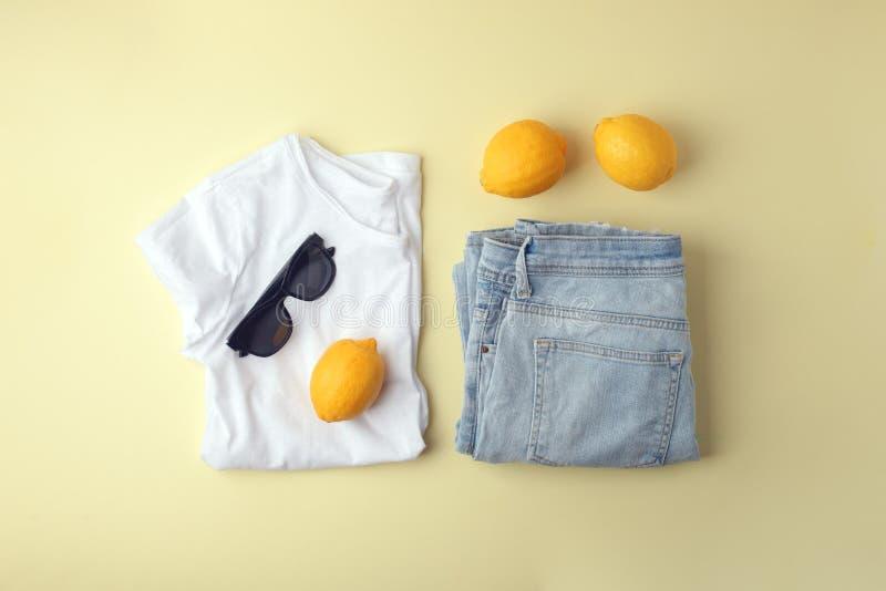 Niebiescy dżinsy, biała koszula, okulary przeciwsłoneczni i cytryny na żółtym tle, Kobiety wiosny lata elegancki str?j Modny odzi obrazy stock