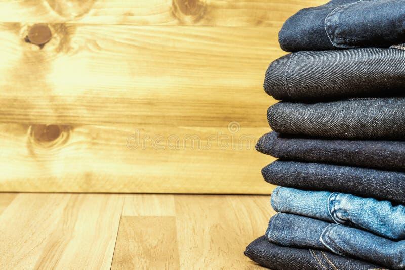 Niebiescy dżinsy na brown drewnianym tła i niebiescy dżinsy drelichu Col zdjęcie royalty free