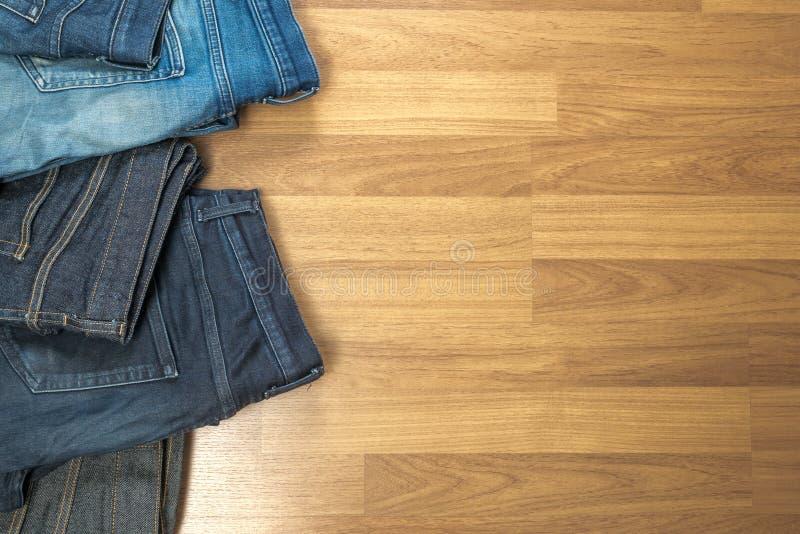 Niebiescy dżinsy na brown drewnianym tła i niebiescy dżinsy drelichu Col zdjęcia stock