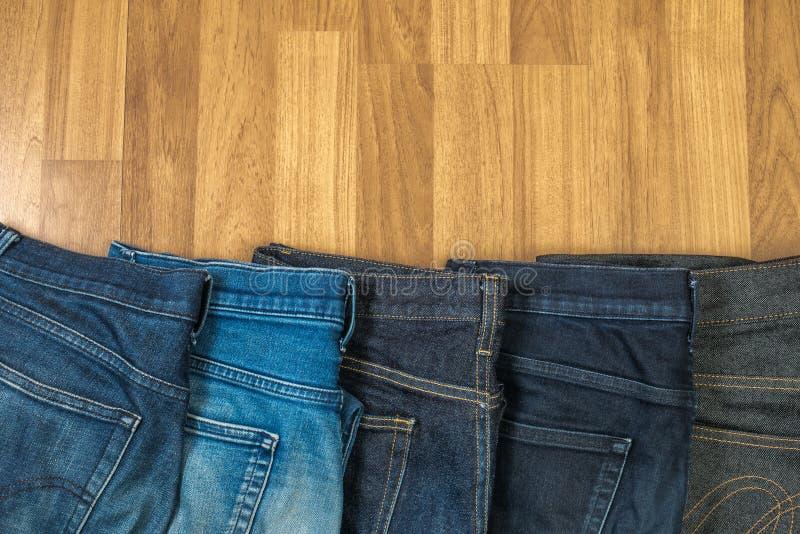 Niebiescy dżinsy na brown drewnianym tła i niebiescy dżinsy drelichu Col fotografia stock