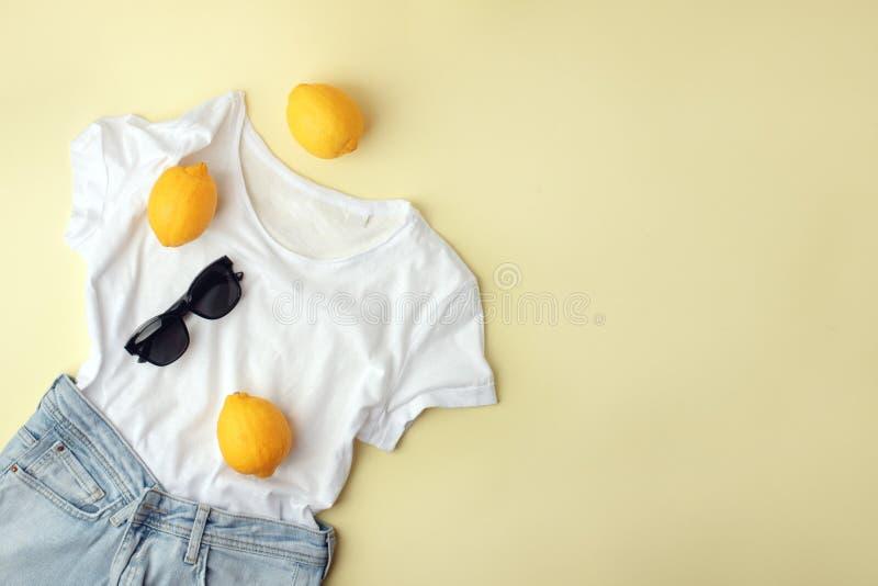Niebiescy d?insy, bia?a koszula, okulary przeciws?oneczni i cytryny na ? zdjęcie stock