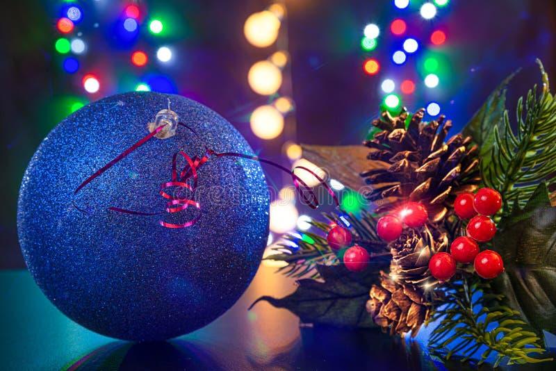 Niebieska kula i gałąź choinki z wybrzuszeniami są na błyszczącym stole/tle Na tle są różne kolory światła zdjęcia royalty free