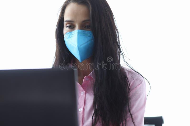 Niebieska maska dla biznesmenki pozwala na korzystanie z notebooka w portrecie zdjęcia stock