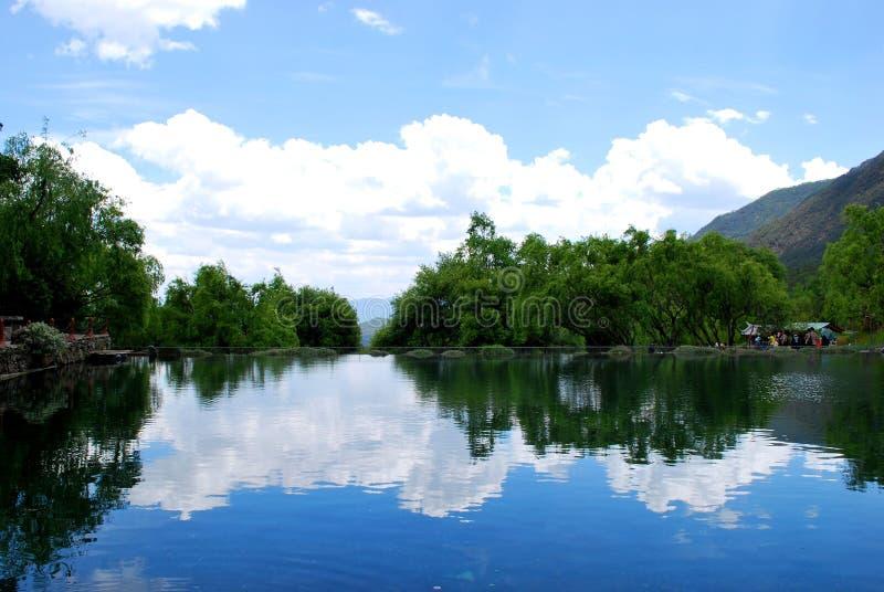 Niebieskie niebo, biel chmury, czyści drzewa, wodni i zieleni fotografia royalty free
