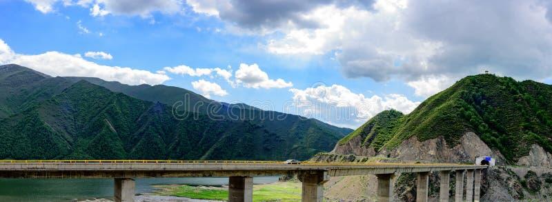Niebieskie niebo, biel chmury, zielone góry i jezioro woda samochodu jeżdżenie z tunelu przyśpieszamy na wiadukcie zdjęcia royalty free