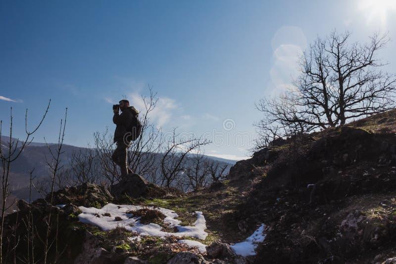 Niebieskie niebo i słońce migoczemy za wycieczkowicz pozycją na wierzchołku góra obraz royalty free