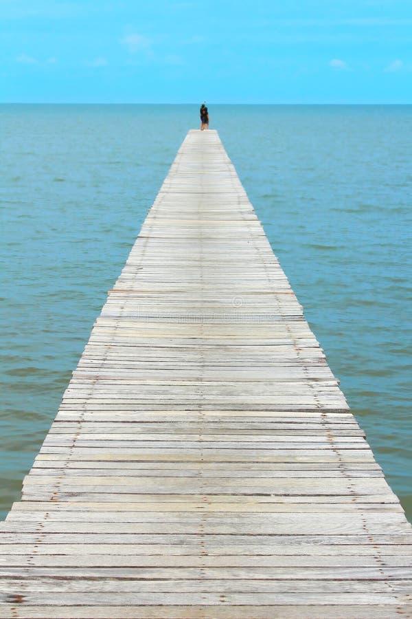 Niebieskie niebo jasny z perspektywicznym drewnianym mostem przedłużyć w morze przy kurortem, pary szczęście i relaksuje w lecie  zdjęcie stock