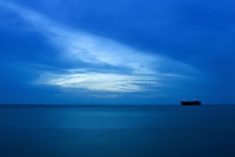 Niebieskie niebo, morze i statek przy nocą, obraz royalty free