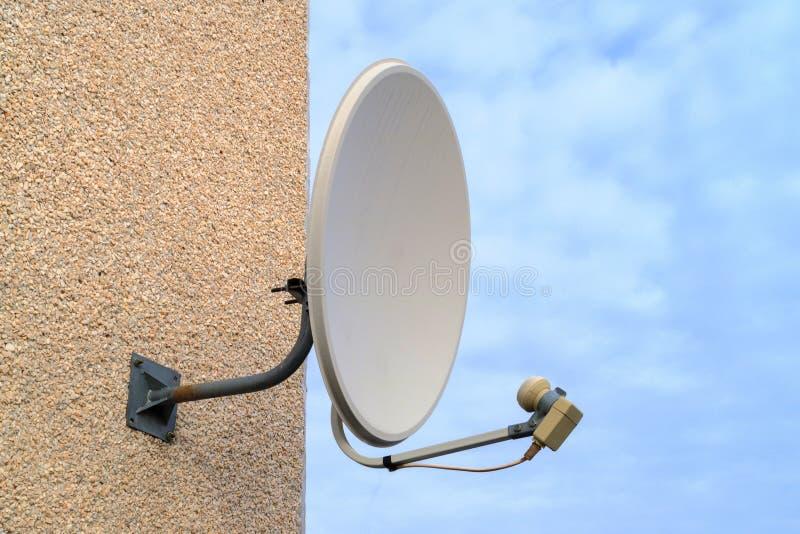 Niebieskie niebo na swój tło białej starej antenie satelitarnej na kondygnacja budynku obrazy stock
