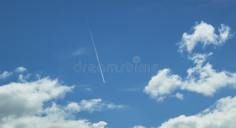 Niebieskie niebo z biel chmurami i latanie samolotem zdjęcie royalty free