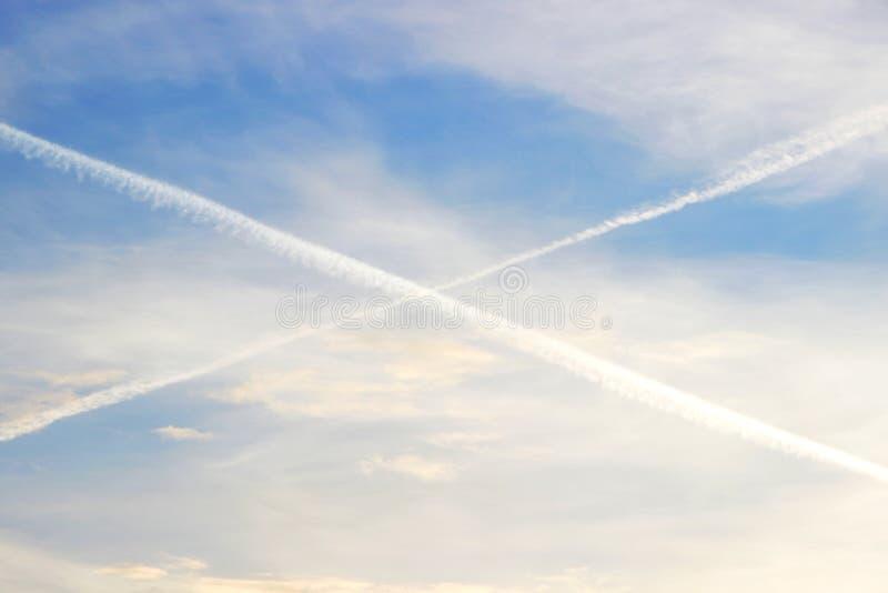 Niebieskie niebo z chmurami, ślada samolotu remisu przekątna wykłada w niebie, przekątna krzyż zdjęcie royalty free