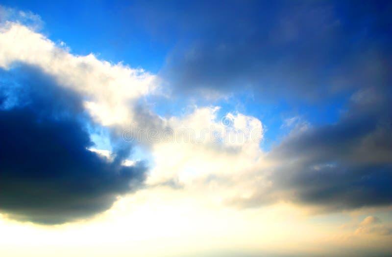 Niebieskie niebo zakrywający z zmroku i światła chmurami obrazy royalty free