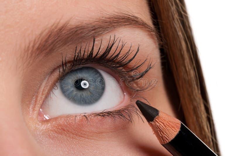 Niebieskie oko, kobieta stosować makijażu czarny ołówek zdjęcie stock
