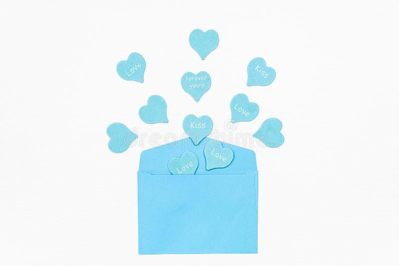 Niebieskie serca z tekstem LOVE, KISS, FOREVER TWOJE wychodzą z niebieskiej koperty na białym tle Prezent dla kochanka spowiedź m zdjęcie stock