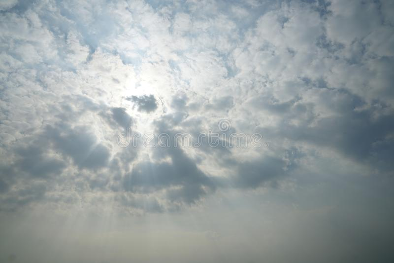 Niebieskiego nieba tło z biel chmurami i słońce promieniem zdjęcie stock