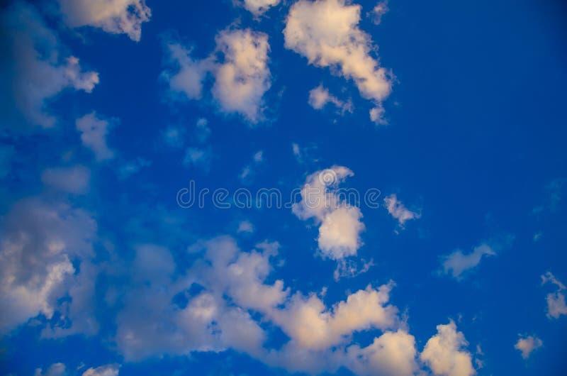 Niebieskiego nieba tło z kolorowymi chmurami fotografia stock
