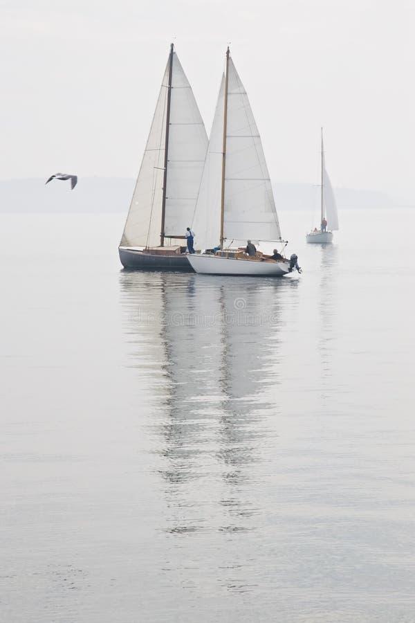 Niebla de agua tranquila de los barcos de vela fotografía de archivo libre de regalías