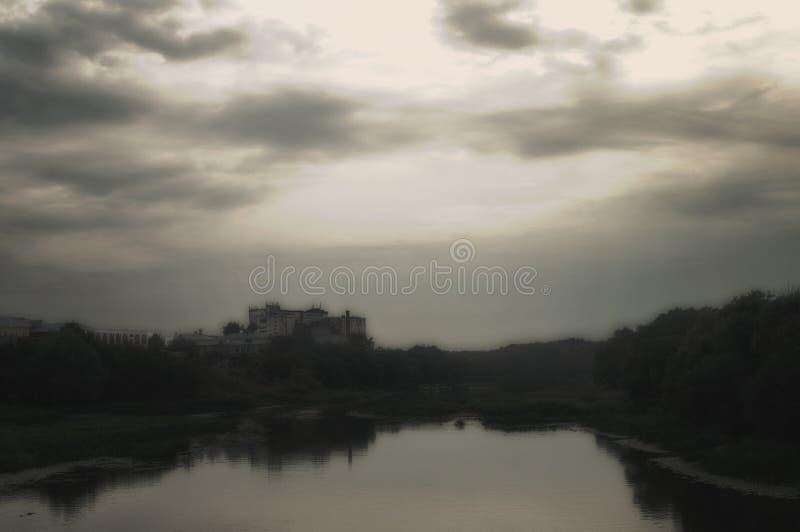 Niebla de la tarde sobre un río de niebla melancólico Cielo nublado y edificios asustadizos en el fondo foto de archivo