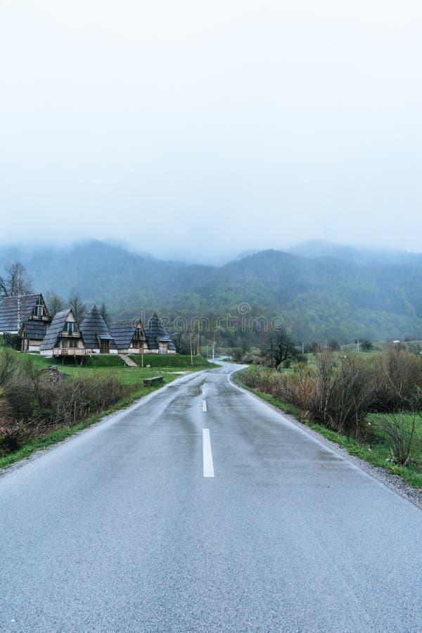 Niebla del paisaje en el pueblo de montaña en el lado del camino Camino mojado en Montenegro imágenes de archivo libres de regalías