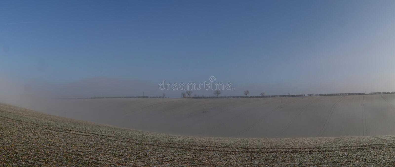 Niebla que sube sobre la tierra arable escarchada fotos de archivo libres de regalías