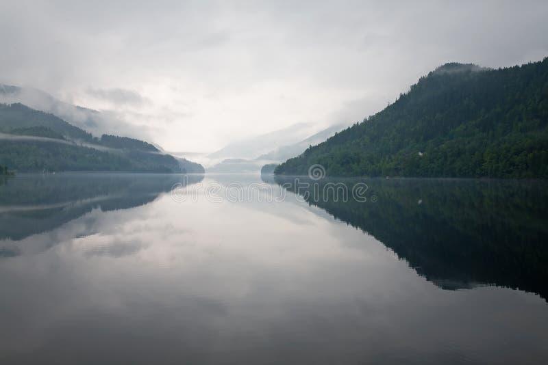 Niebla sobre el agua y las montañas fotos de archivo