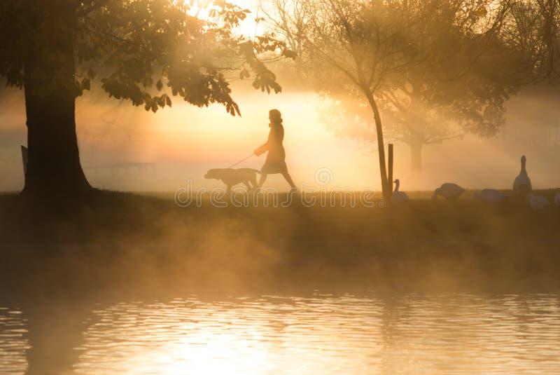 Niebla y niebla de la madrugada sobre el lago con los transeúntes cerca foto de archivo libre de regalías