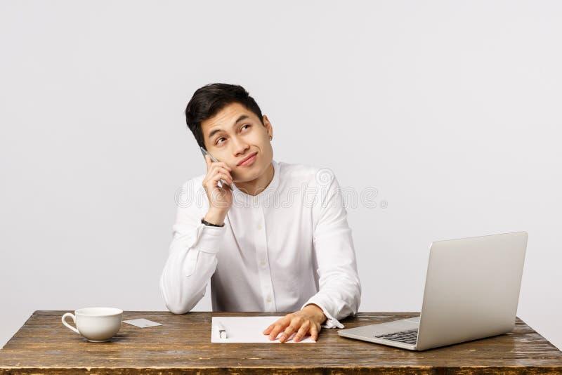 Niechętny, przystojny chiński przedsiębiorca w białej koszuli, stolik w biurze z laptopem, dokumenty raportów obrazy royalty free