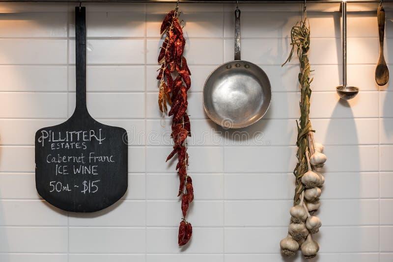 Niecka, drewniana łupa, metal zupna łyżka, wysuszony czerwony pieprz i czosnku obwieszenie od białej ściany, obrazy stock