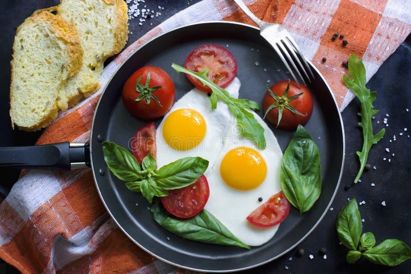 Niecka smażący jajka, basil i pomidory z chlebem na grunge kruszcowym stole, ukazujemy się obraz stock