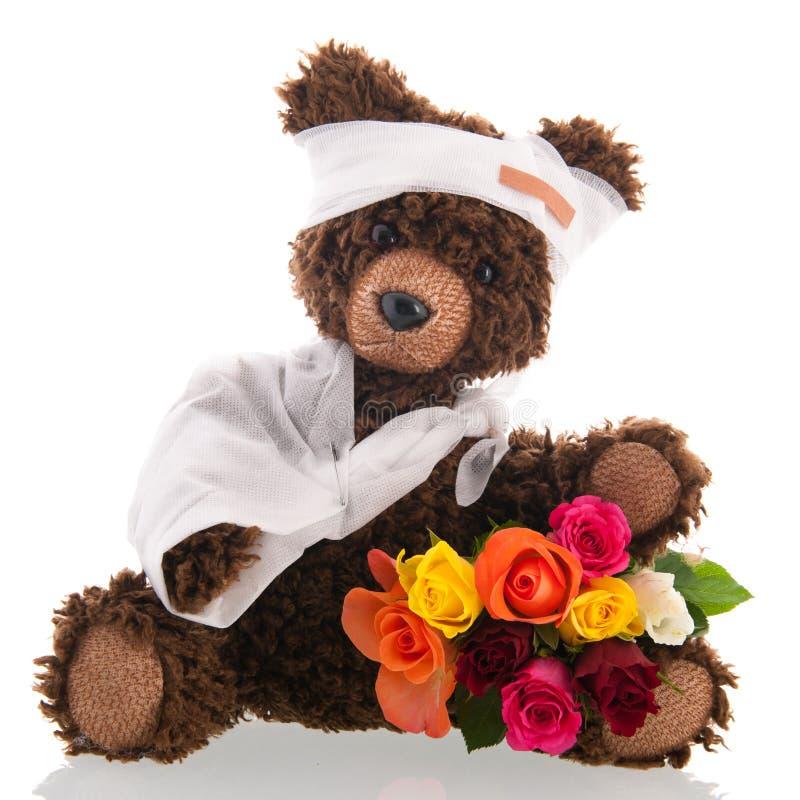 Niedźwiedź z bólem i kwiaty odizolowywający nad białym tłem zdjęcia royalty free