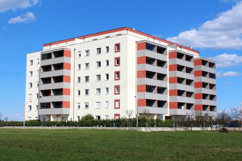 Niedawno budujący nowożytny budynek mieszkaniowy z wieloskładnikowymi mieszkaniami i balkonami otaczającymi z trawą i małym żywop obrazy stock