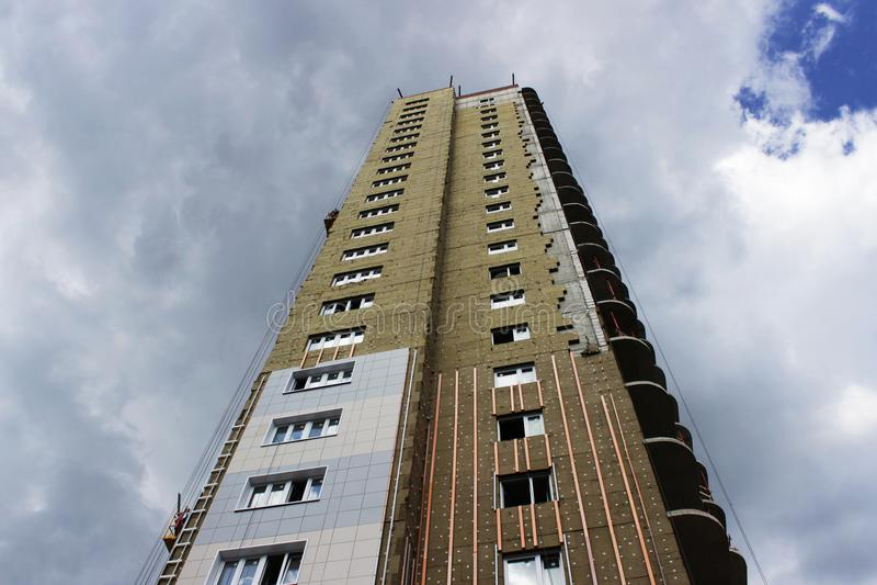 niedawno budujący wieżowiec z izolować ekologicznych nowożytnych panel na niebieskiego nieba tle obraz royalty free