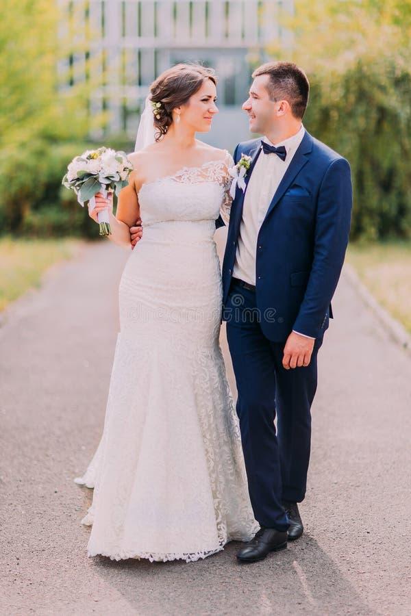 Niedawno para małżeńska pozuje w pogodnym parku przy aleją Beautyful panna młoda trzyma jej bridal bukiet fotografia stock