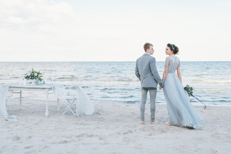 Niedawno pary małżeńskiej mienia ręki morzem fotografia stock