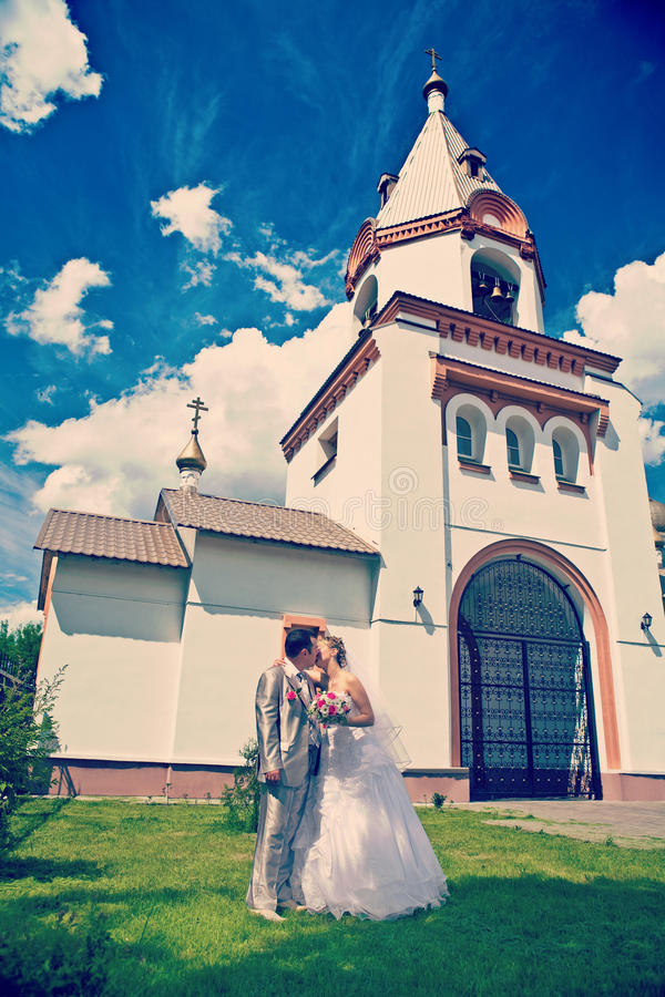 Niedawno zamężny całowanie na tle kościelny śródpolny instag obrazy stock