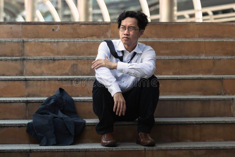 Niedergedrückt betonte jungen asiatischen Geschäftsmann in der Klage mit den Händen auf dem Kopf, der auf Treppe sitzt Arbeitslos lizenzfreie stockfotografie