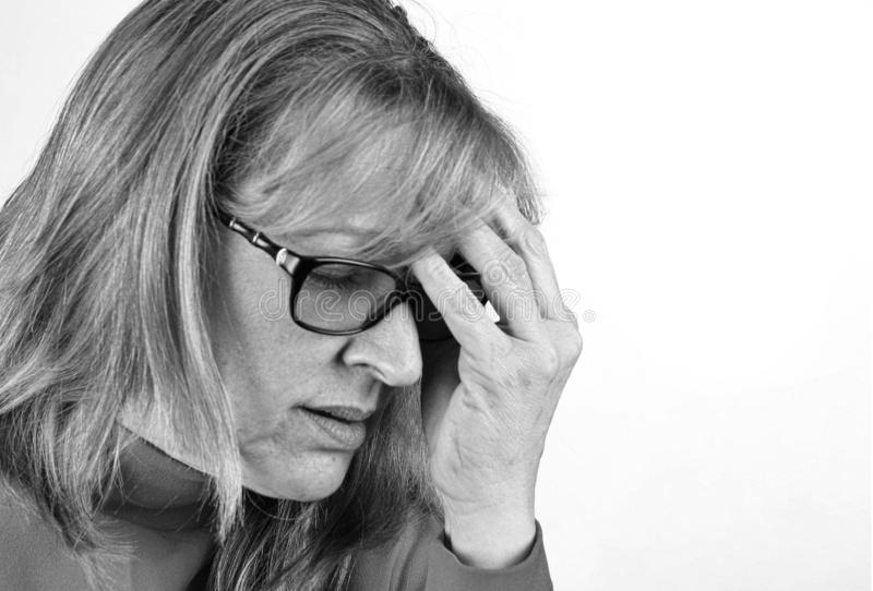 Niedergedrückte, besorgte Frau mit der Hand auf Kopf Schwarzweiss lokalisiert mit Kopienraum stockfoto
