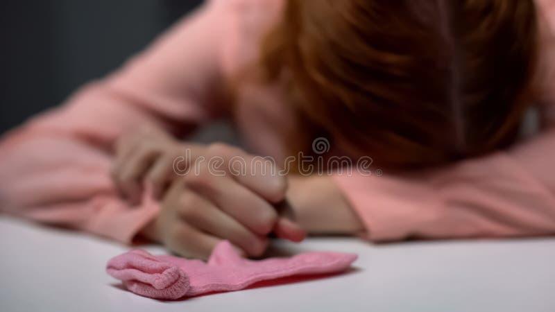Niedergedrückte junge Dame, die in der Verzweiflung, rosa Kindersocke auf Tabelle, Unfruchtbarkeit schreit stockfotos